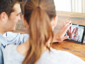A young couple using a digital tablet for a video call with their family